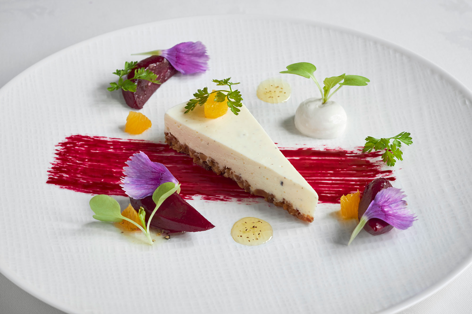 Dessert displayed on a white plate with colorful garnishes of vibrant purples, oranges and greens.