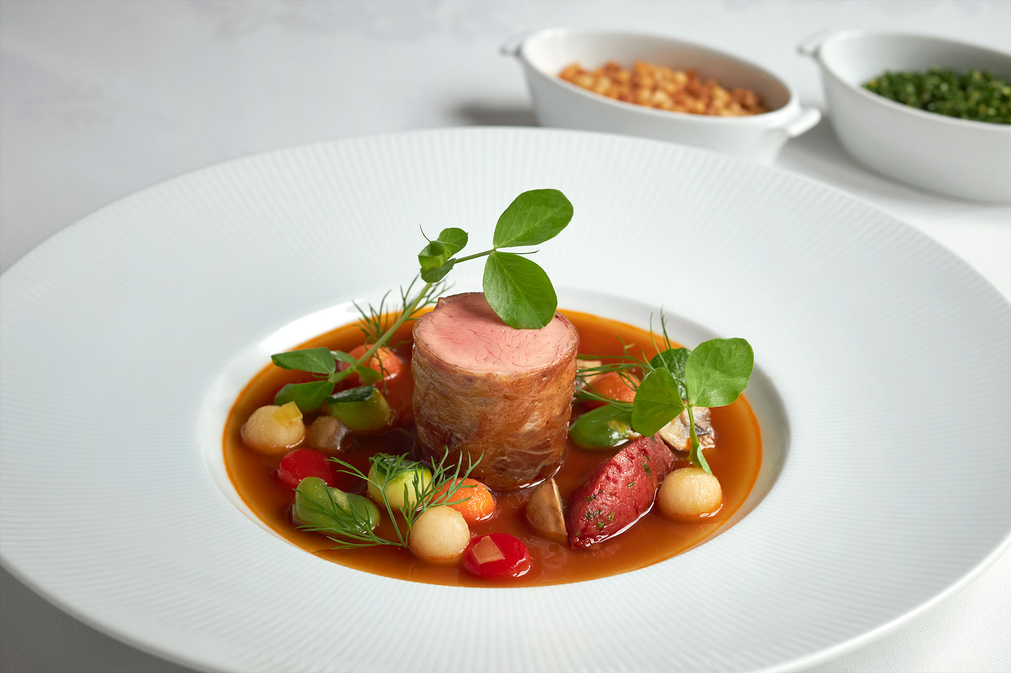 Prosciutto-Wrapped Veal Tenderloin in a Fragrant Broth Perfumed with Spring Vegetables