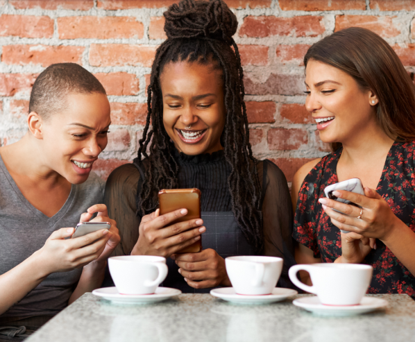 Three women with their phones around a coffee shop table.