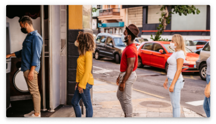 Four people with covid masks waiting to use an ATM.