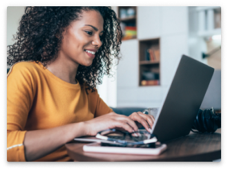 A woman smiling while working at her computer.