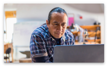 A Native American man working at his computer.