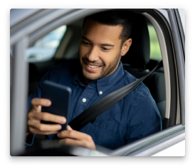 A man in his car with his smartphone.