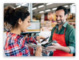 A woman using contactless payments to buy groceries.