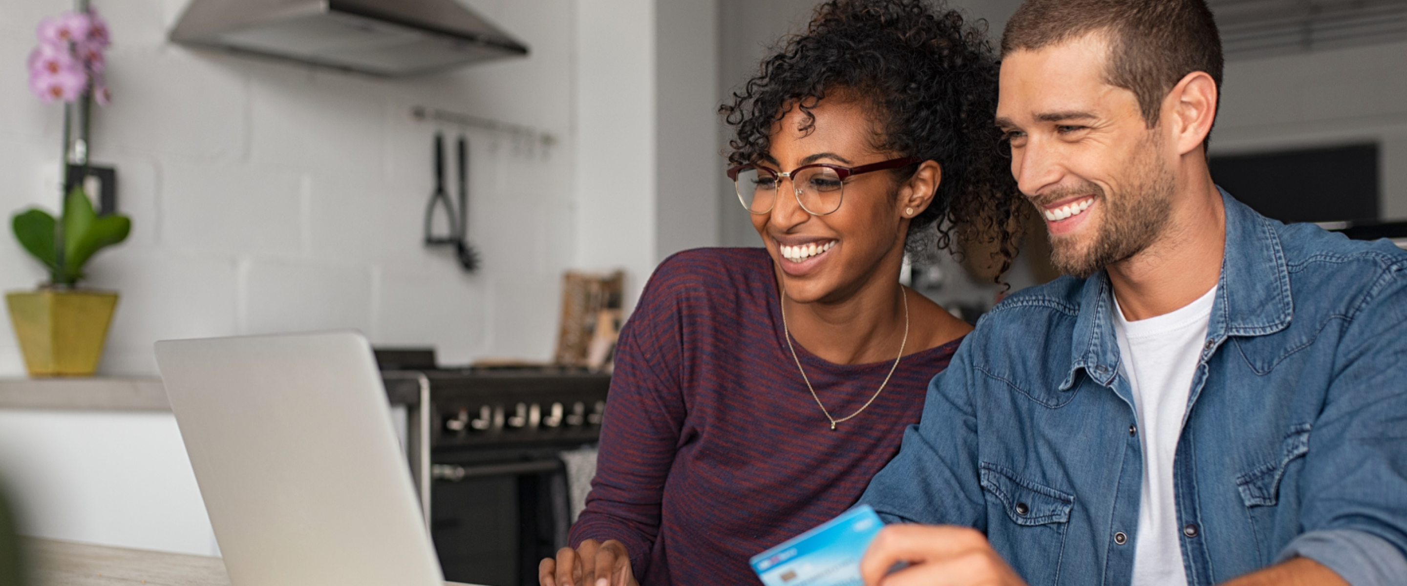 Two people with a debit card looking and smiling at a laptop computer.