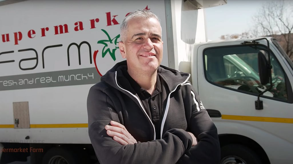 An image of Nelson Duarte from the Supermarket Farm standing in front of a company refrigerated truck