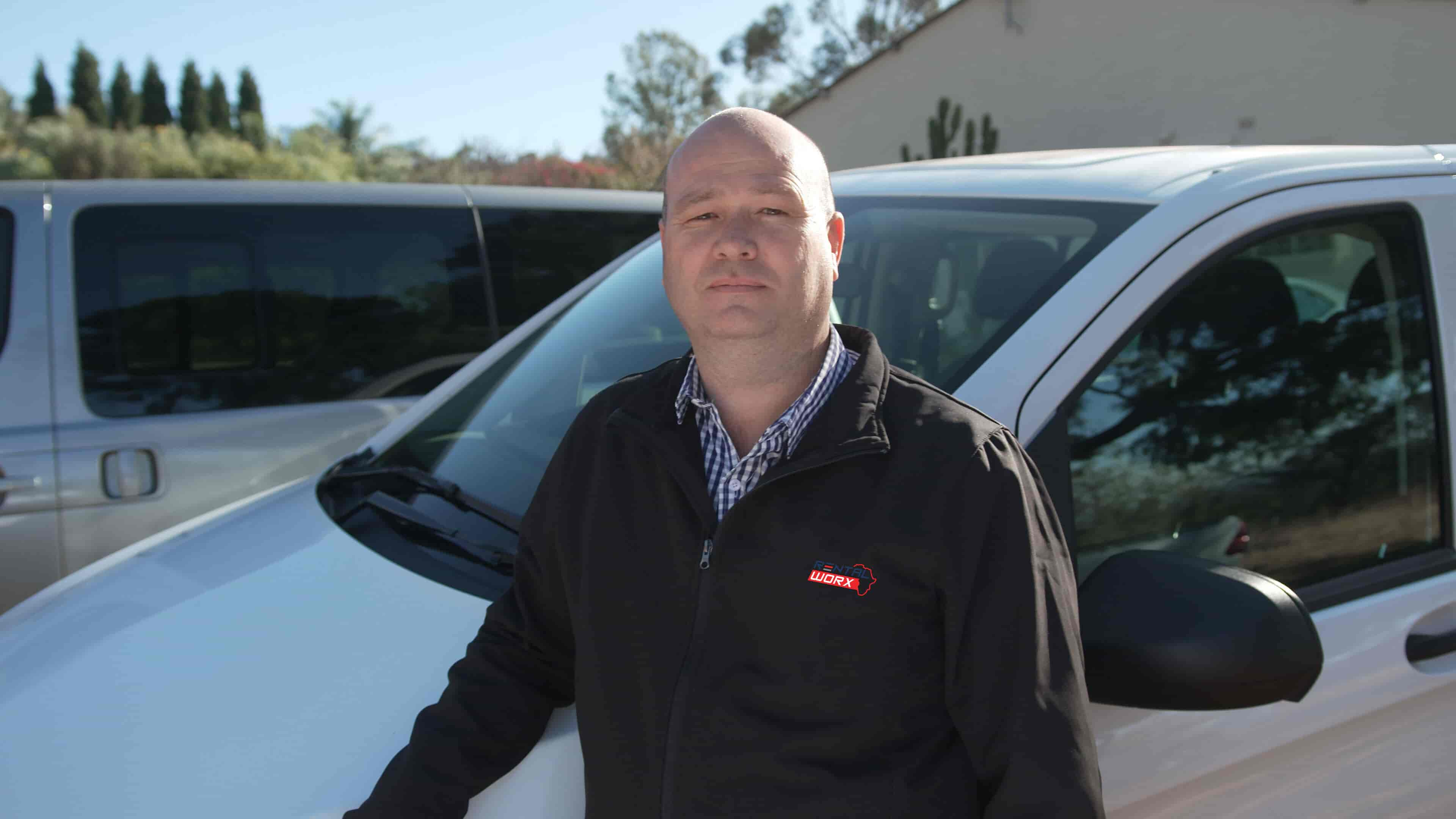 Johan Kruger from RentalWorx, a leasing company, stands in in front of his company's rental passenger van.