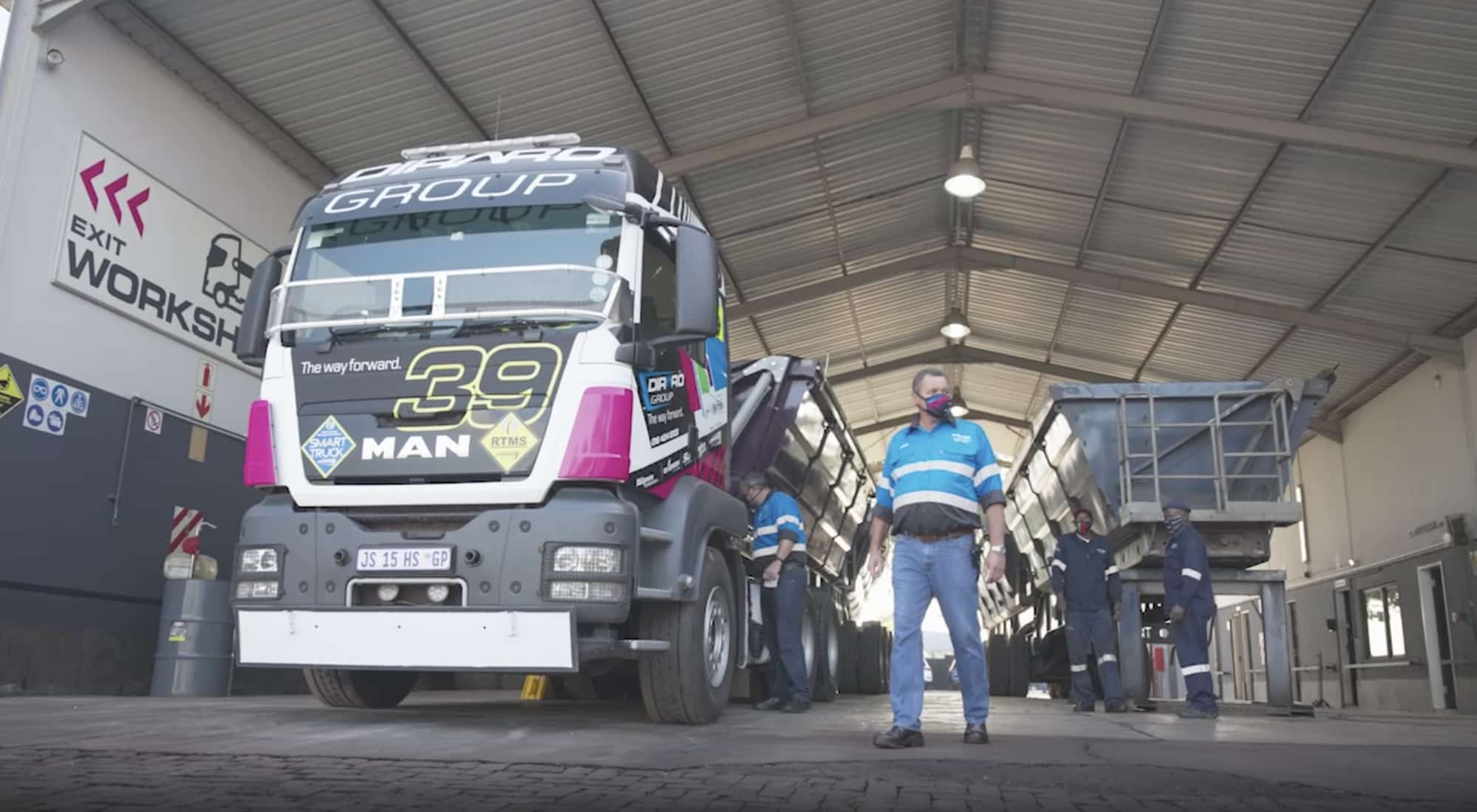 Louw Riekert from logistics company Diraro stands in front of the company's Man Truck with his team in the background.