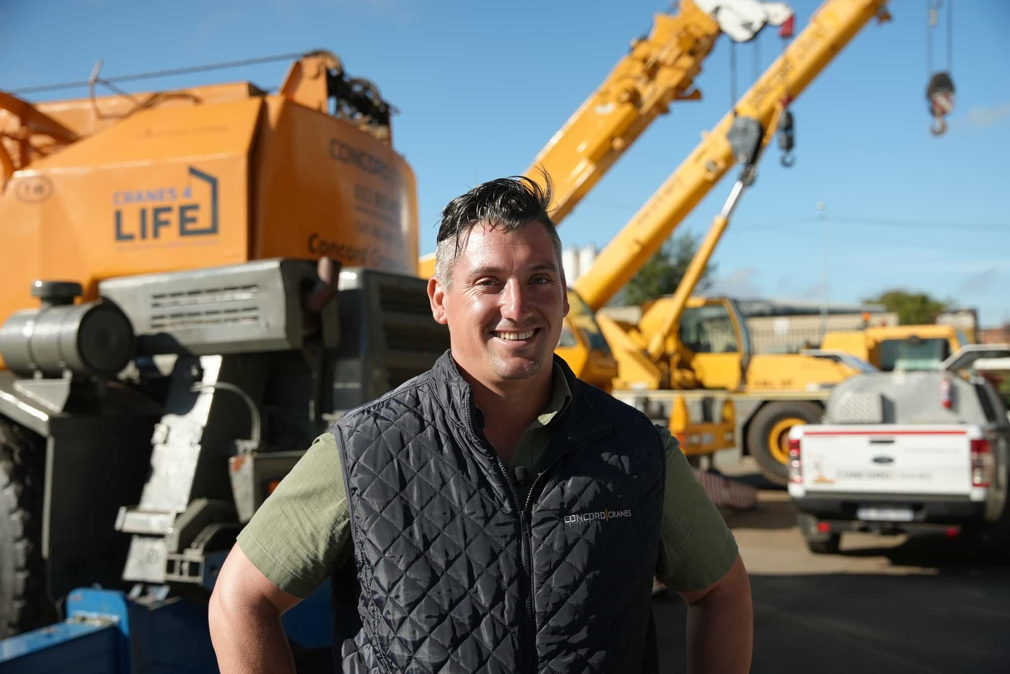 A picture of the operations manager of Concord Cranes, Gareth Langley, with their construction fleet in the background.