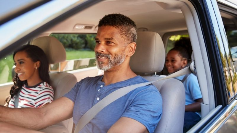 A family of a dad, mom and daughter driving in the car with smiles