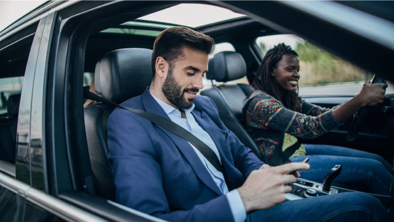 A happy couple drive in the car that is tracked with a gps solution as they husband completes his SARS compliant vehicle logbook via a mobile app.