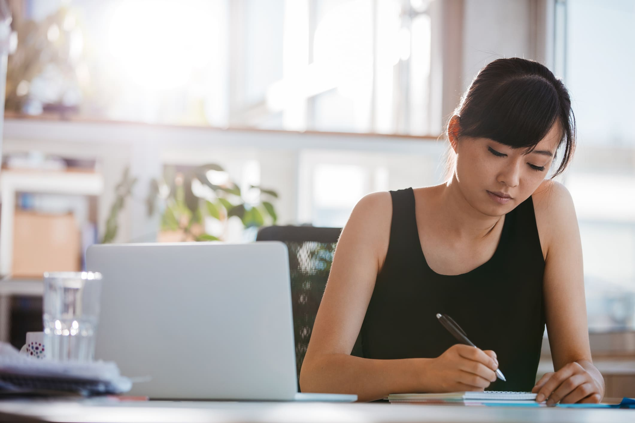 Who determines your IR35 status and who pays employment taxes, image of a women writing at a desk | Crunch