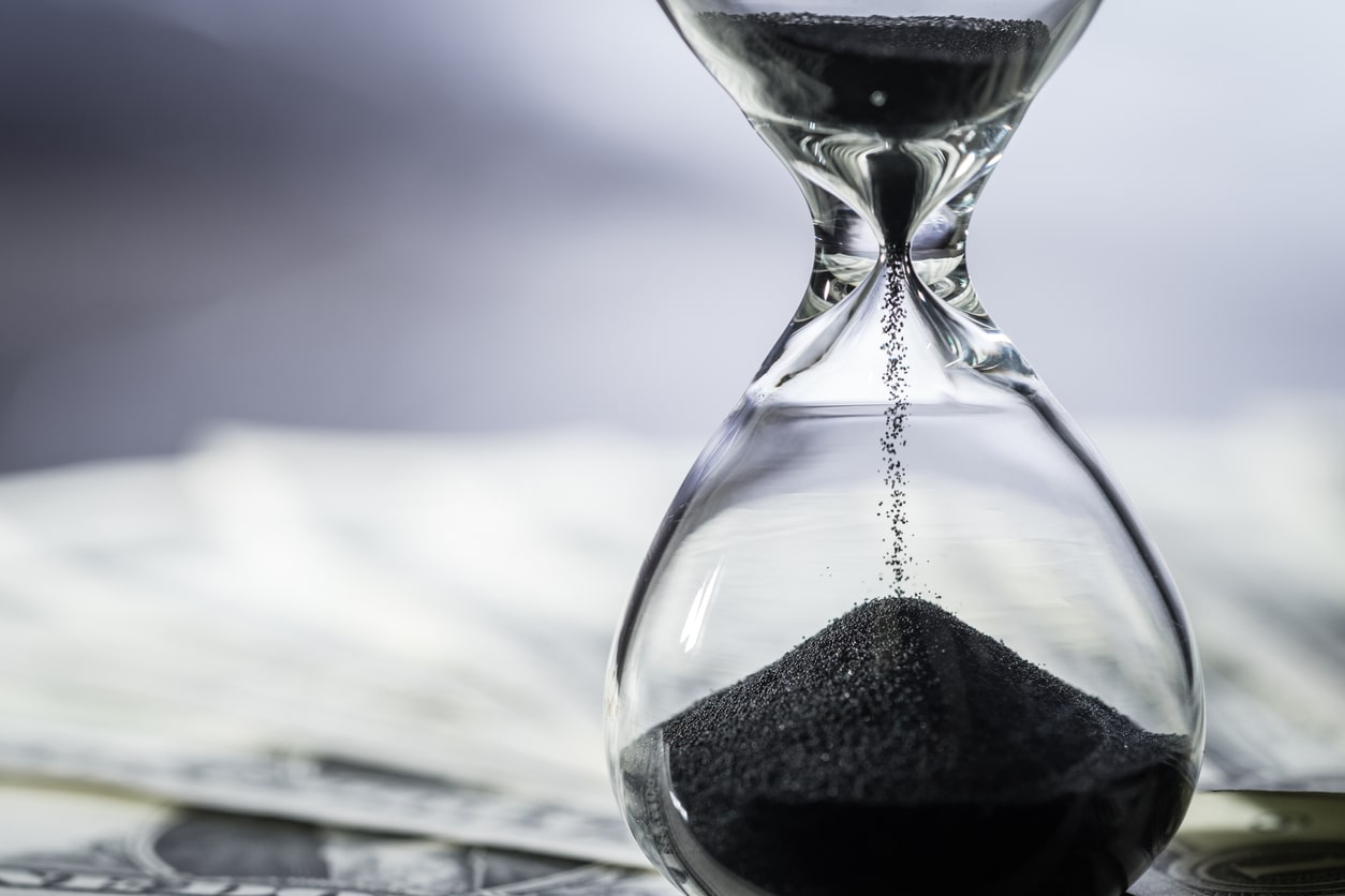 Short-time working and lay-offs (information for employees). Image of an hourglass on a bed of money