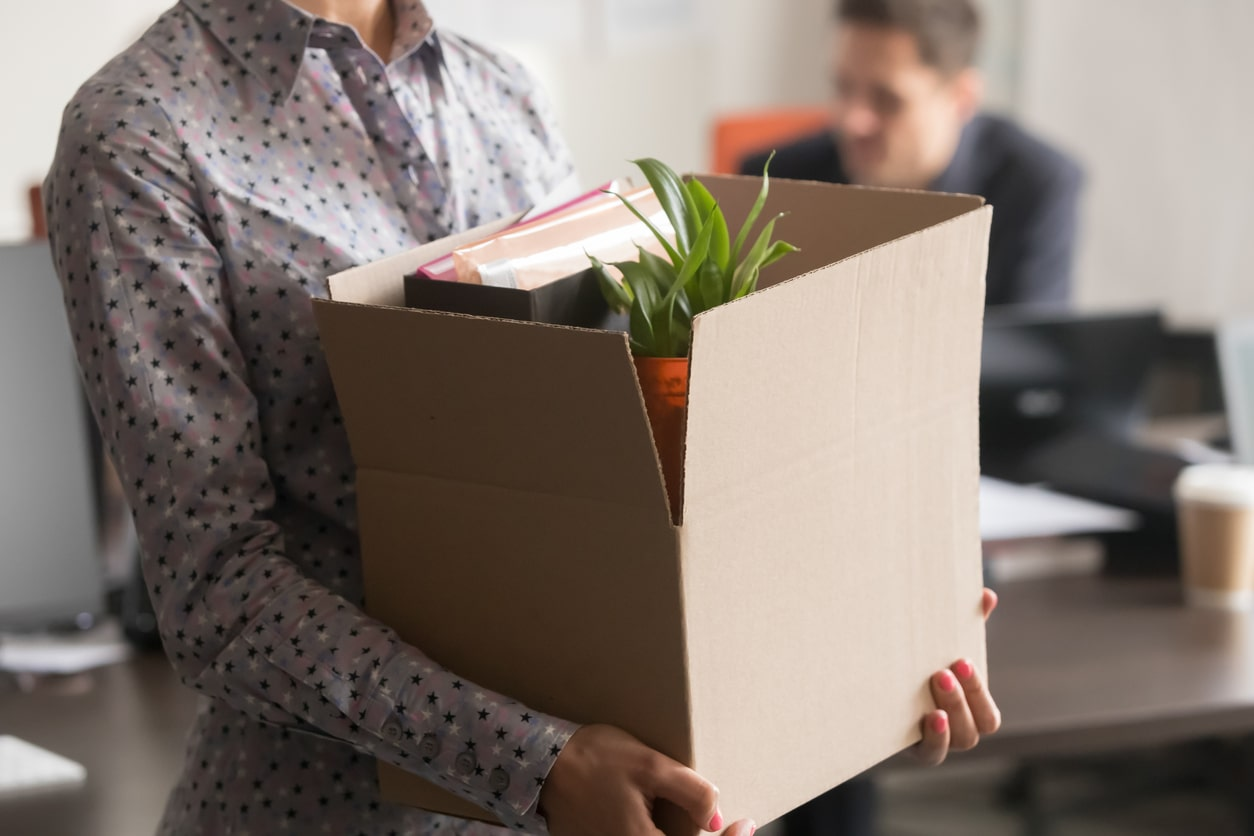 Your employer is making you redundant but has offered you another job – must you accept it?. Image of woman packing up her desk | Crunch