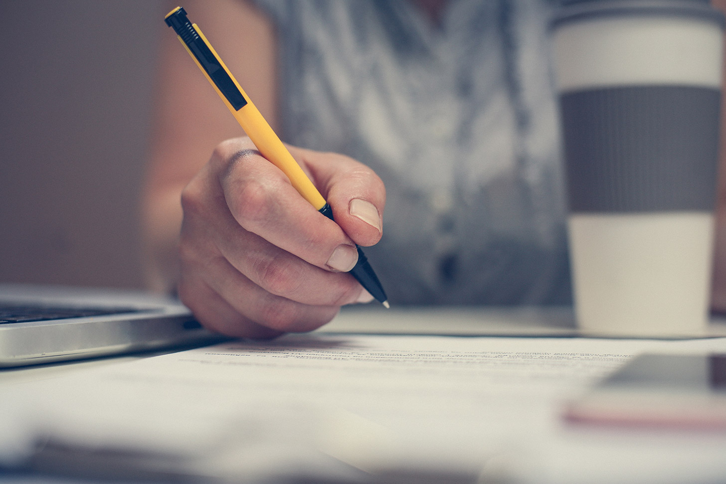 Am I an employee, self-employed, or a worker?, image of someone writing with a coffee cup by them | Crunch