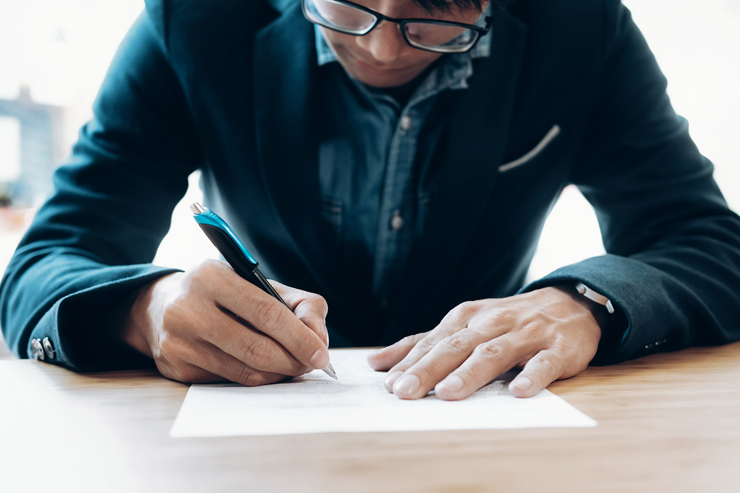 Fixed Term Contracts: what are they & how can they come to an end?, image of a businessman signing contract | Crunch
