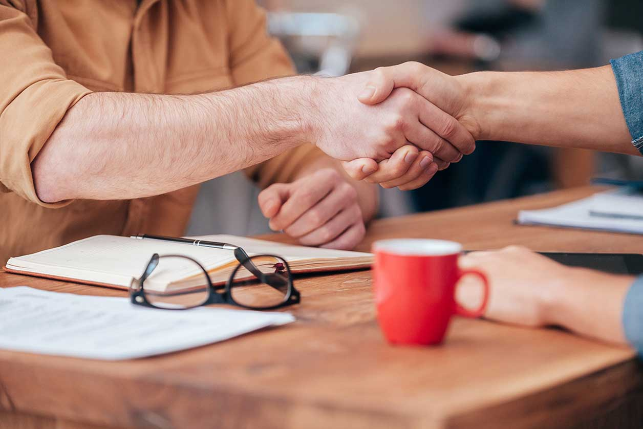 How much does it cost to hire an employee?, image of a handshake | Crunch