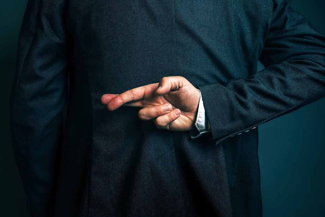 Trust and confidence - what does it really mean and what happens when it breaks down? Image of a man crossing his fingers behind his back | Crunch