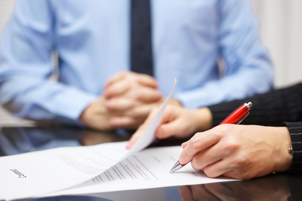 Custom and practice, and employment contract terms (implied and express terms) Image of someone signing a contract