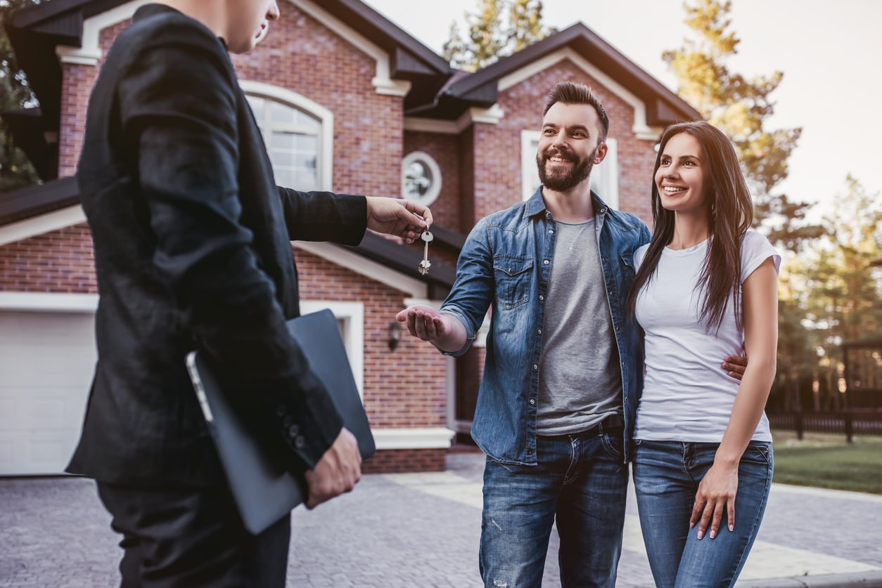 What is an umbrella company mortgage?, image of a couple receiving their keys | Crunch
