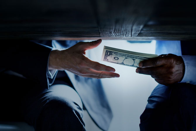The Bribery Act 2010 – honesty is the best policy. Image of someone accepting a bribe