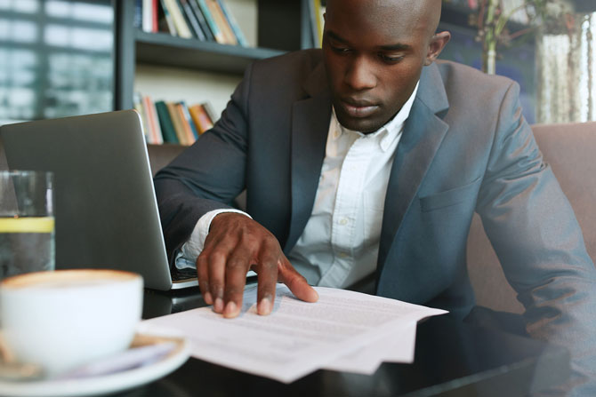 What Is A Shareholders Agreement And Why You Need One. Image of a man reading a book in a cafe.