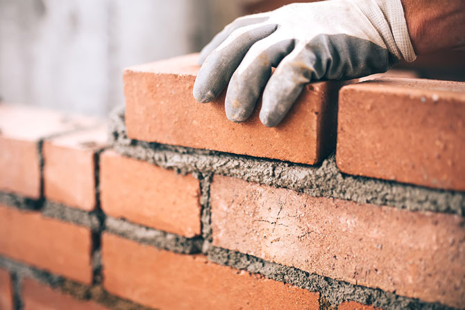 What are the tax implications of paying into a personal pension? (Image of bricklayer building a wall)