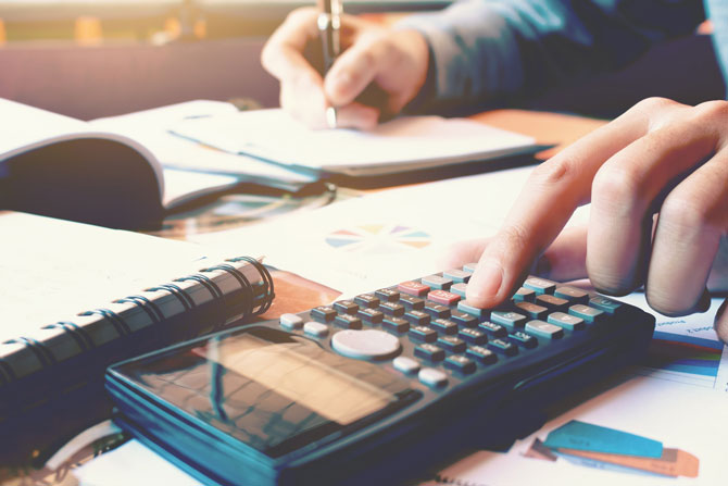 What is Entrepreneurs' Relief when selling shares in your business?, image of a woman using a calculator to work out tax | Crunch