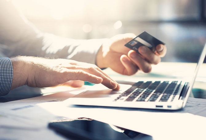 Image of a person paying online with a credit card.