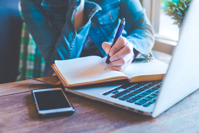 the best portfolio sites for freelance writers - Crunch - image of someone working with a notebook and laptop