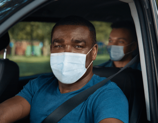 Via driver in car with mask