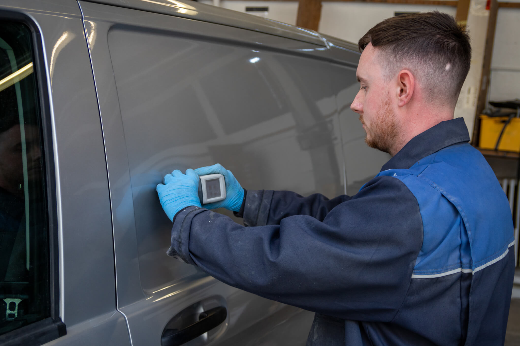 Vehicle repair technician testing the colour of a van