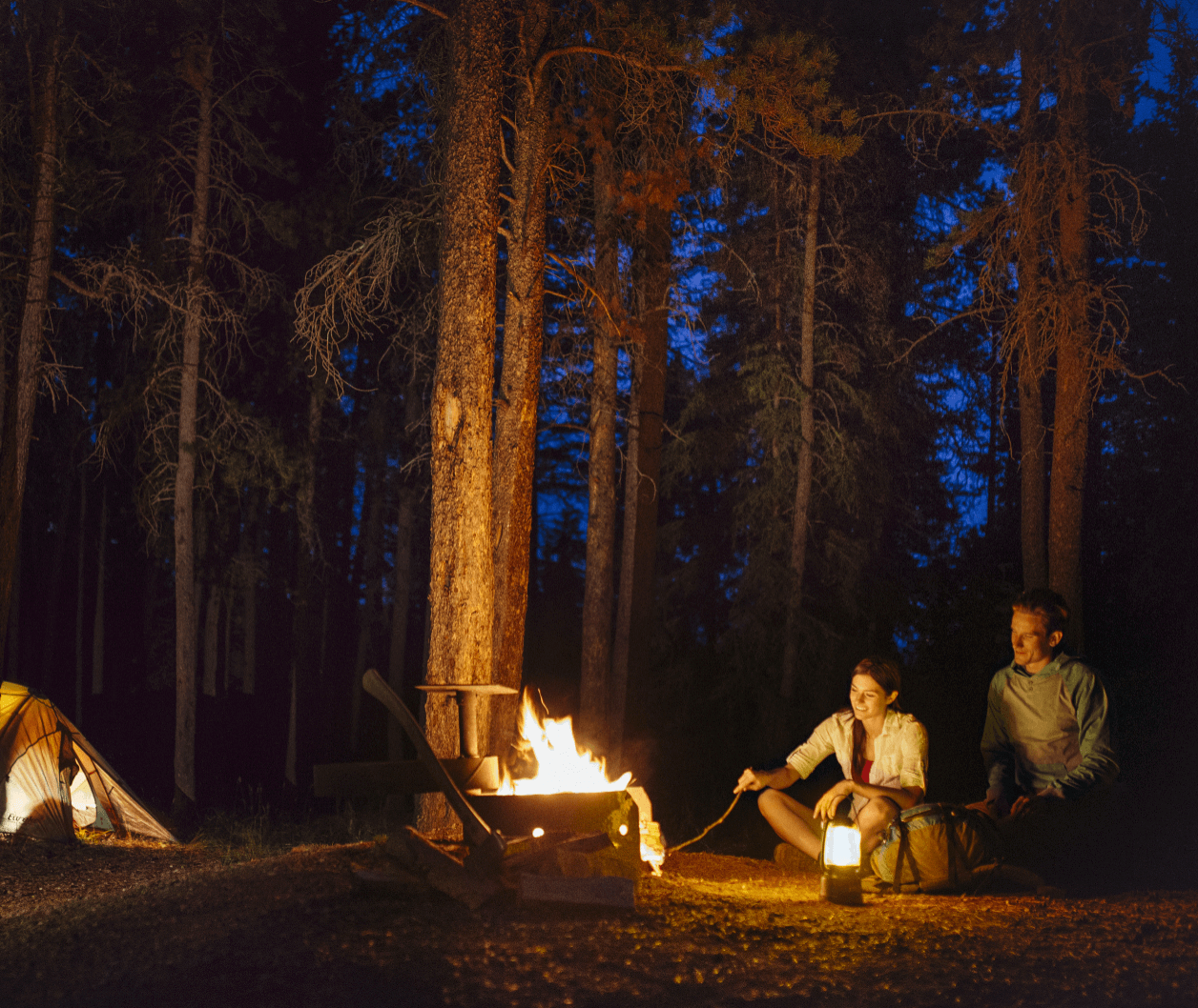 A couple sits by the campfire at a campsite in Cypress Hills Interprovincial Park.