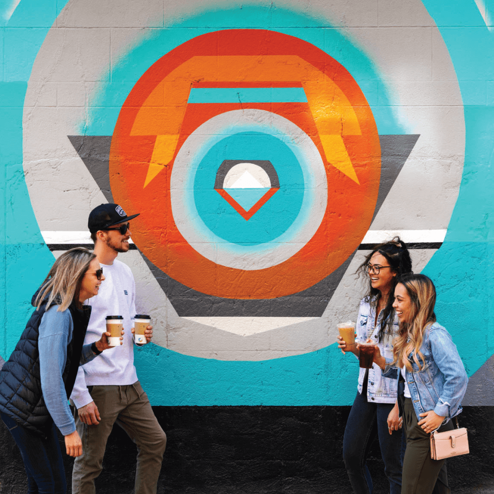 Four art lovers share a laugh next to Exposure, a mural in downtown Medicine Hat.