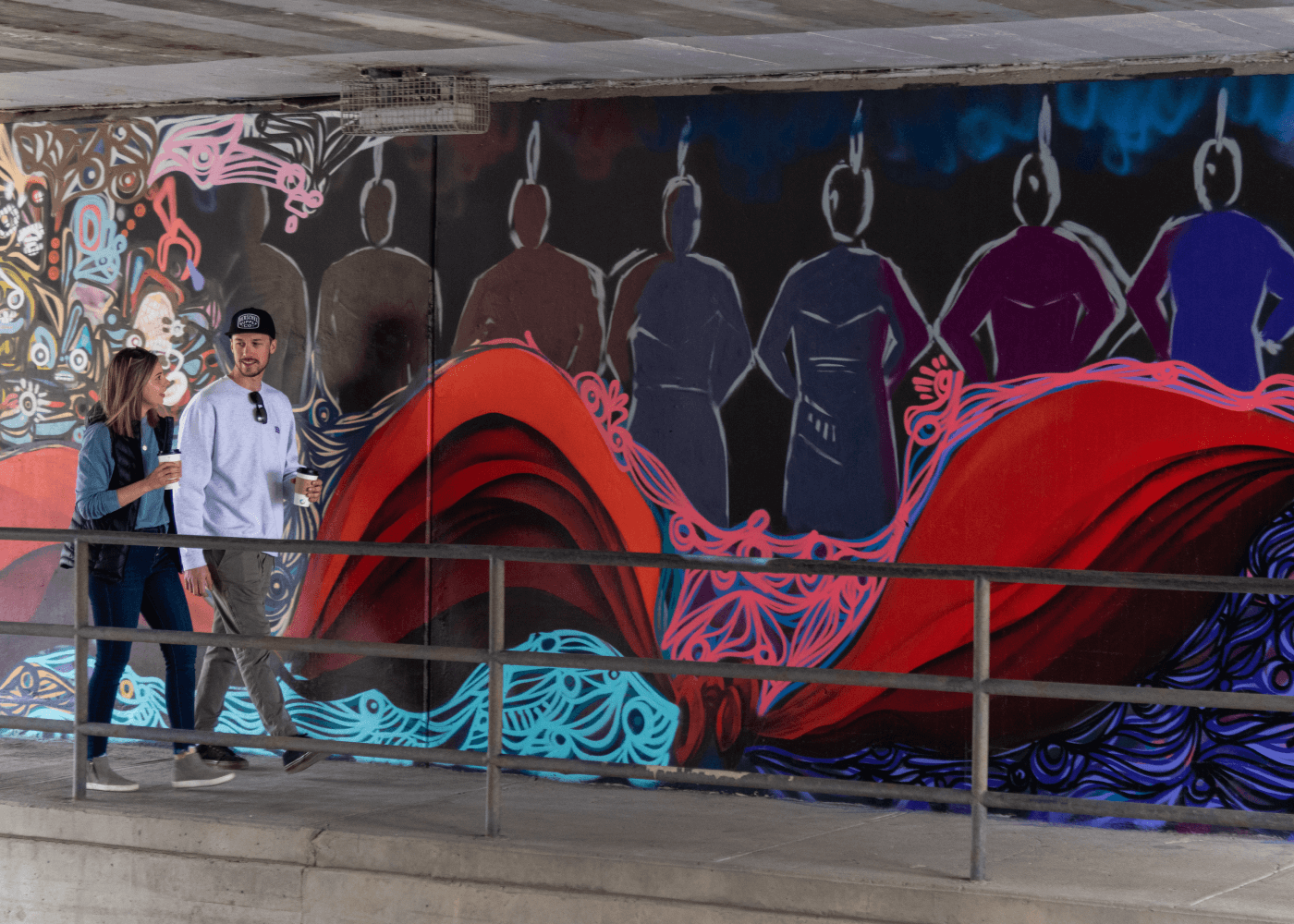 A couple walks past a colourful mural in Medicine Hat