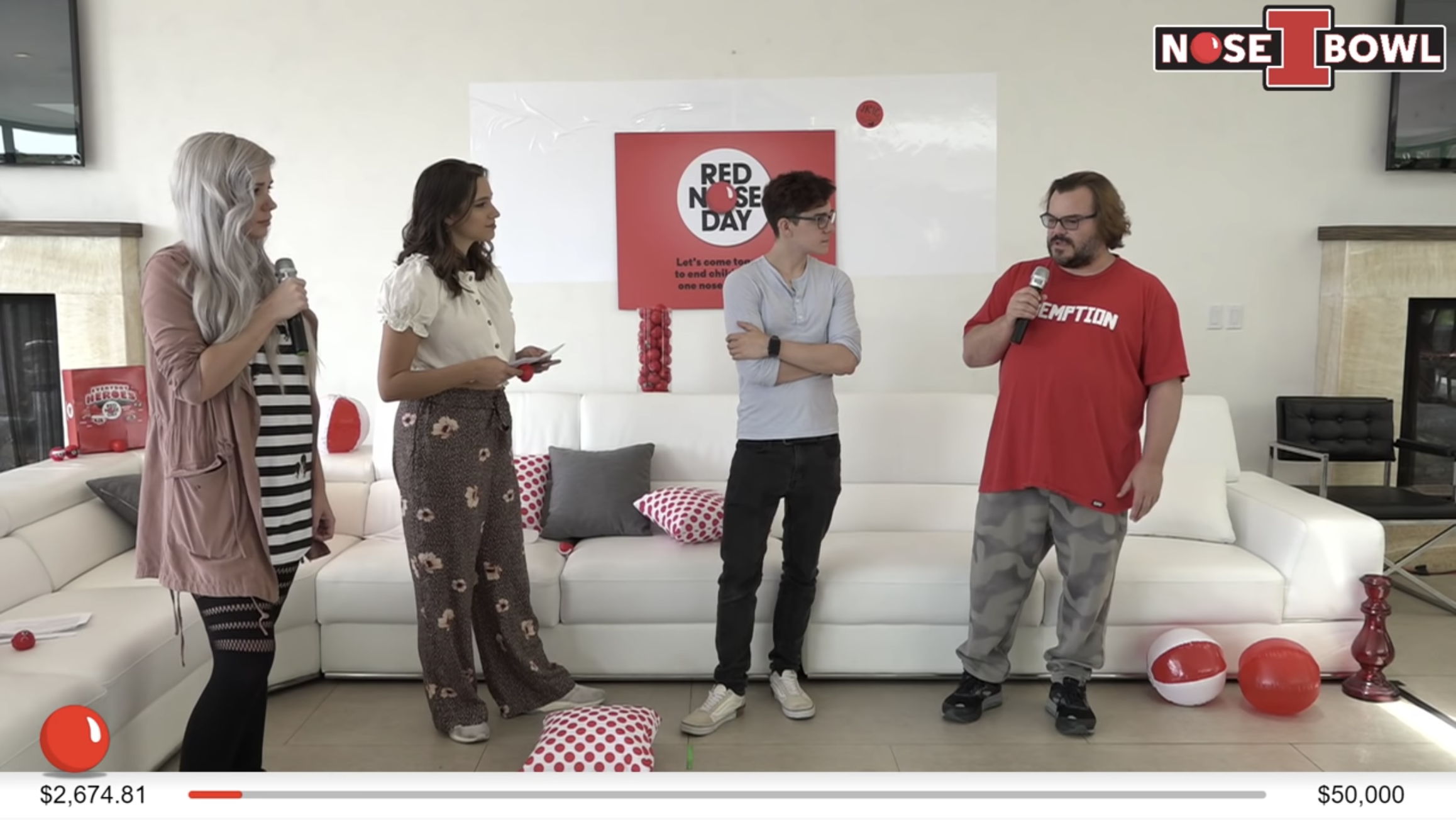 Still image of Red Nose day livestream. Jack Black holds a microphone and talks to three other guests. A live donation meter at the bottom indicates that they have raised $2,674.81 a $50,000 goal.
