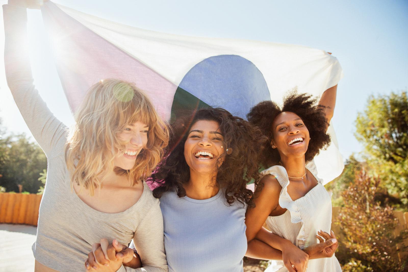 Lifestyle photo of 3 women holding the Alltrue Flag