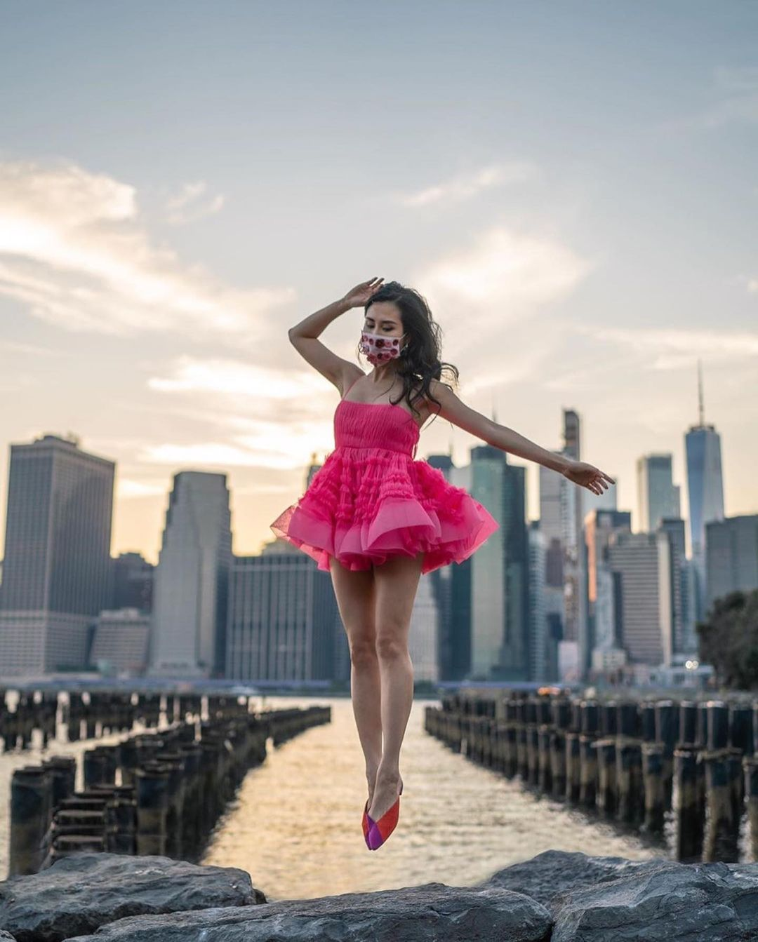 Girl in pink dress in front of city skyline