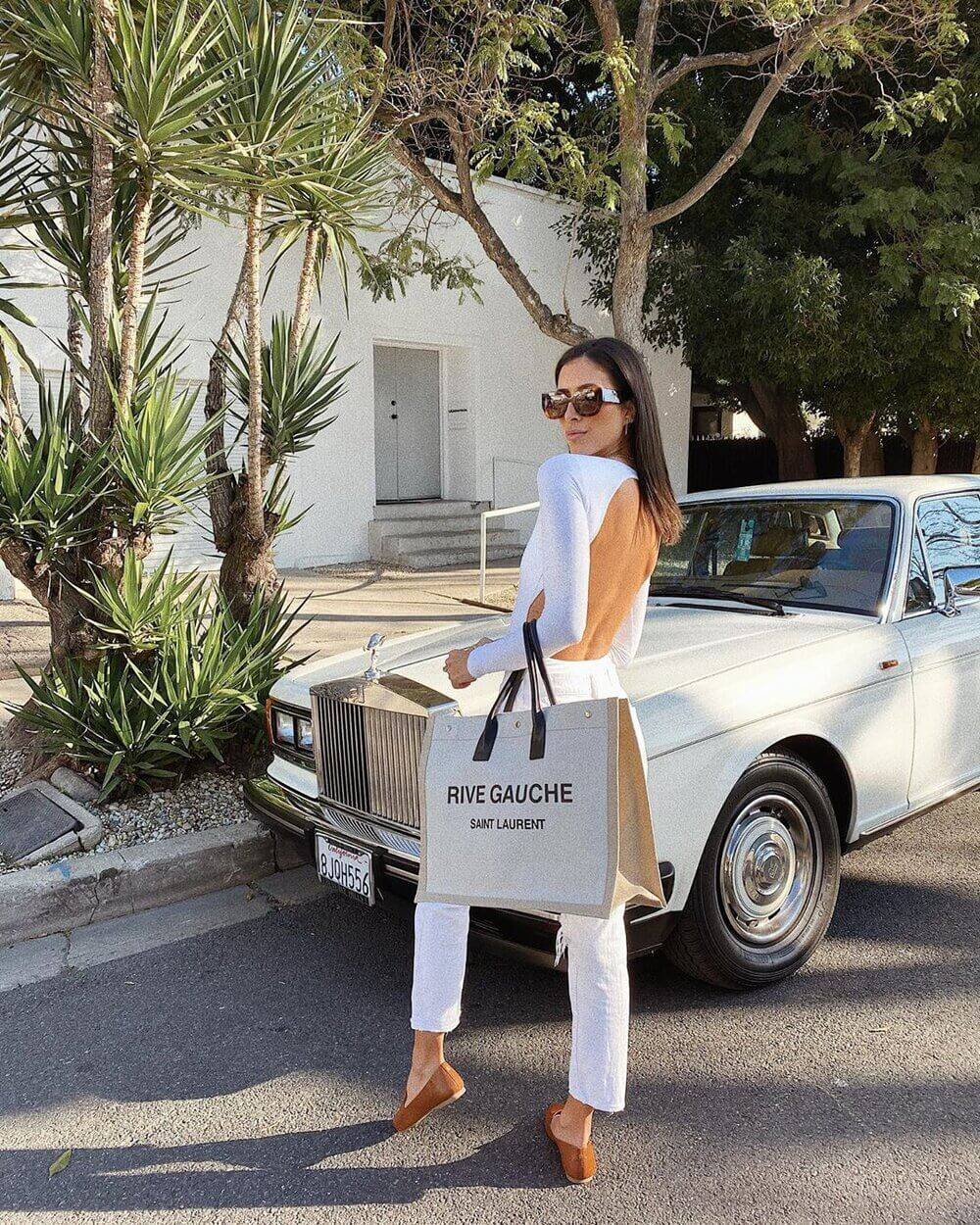 woman with designer bag in front of car