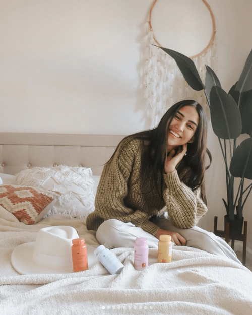 influencer sitting on bed with products