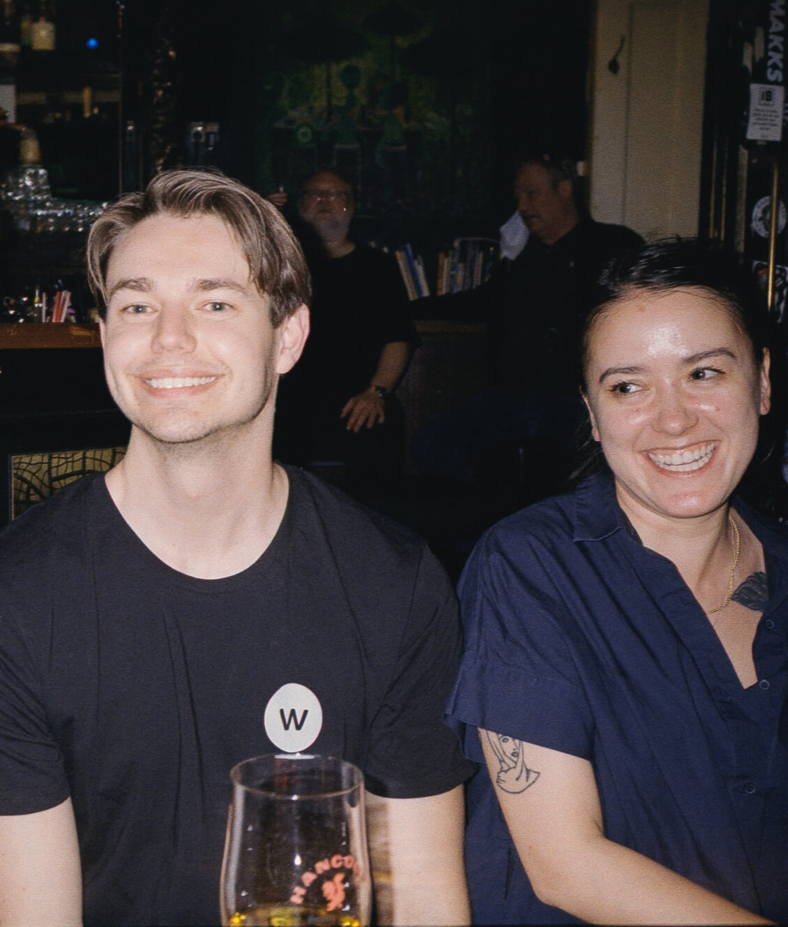 Two Worksome team members (Frederik and Casey) at a bar smiling