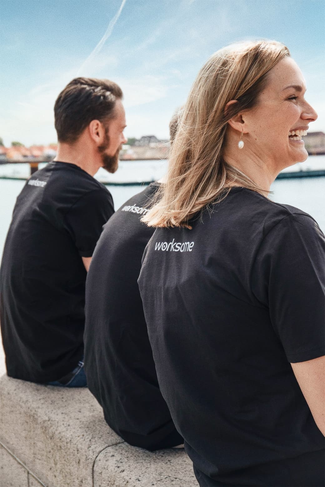 The C.E.O, C.C.O, C.P.O sitting in front of the sea with a worksome tee-shirt