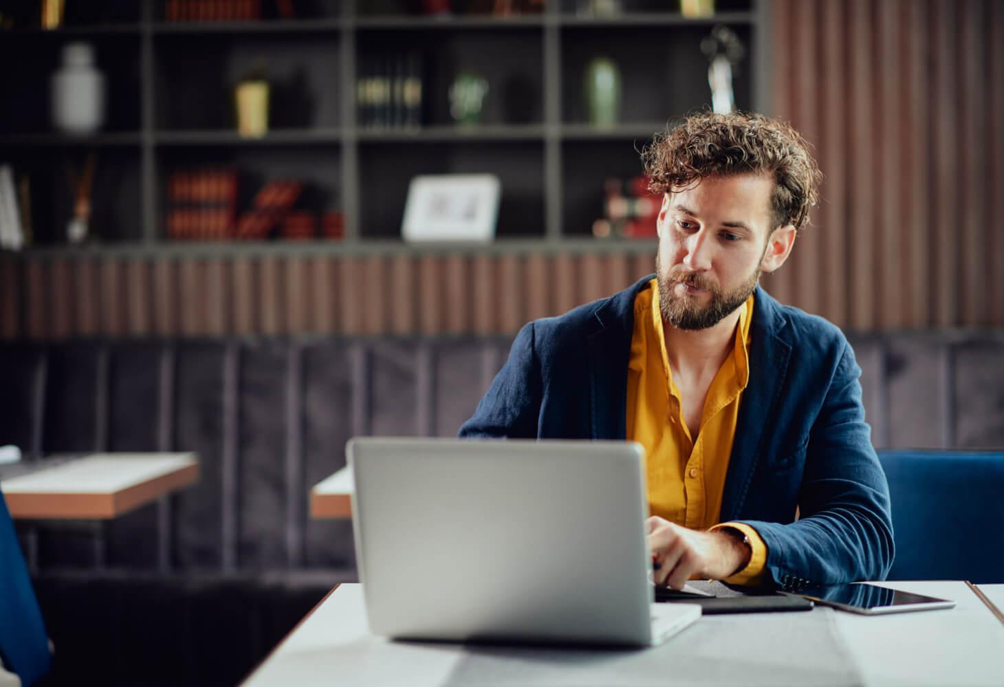 Krögare sitter vid dator och gör schema för personal.