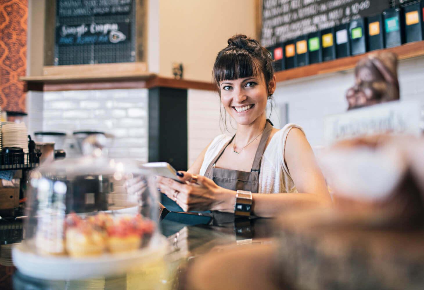 Cafeägare som sköter admin med Caspecos system på en iPad.