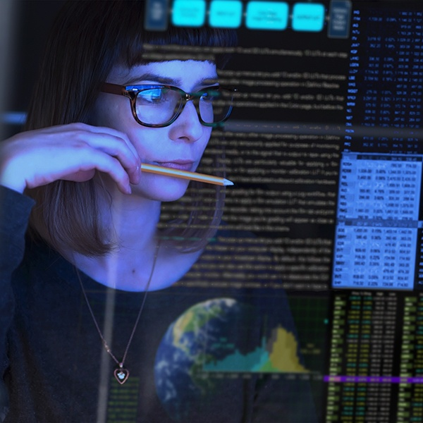 Image of woman holding pencil looking at text on screen.