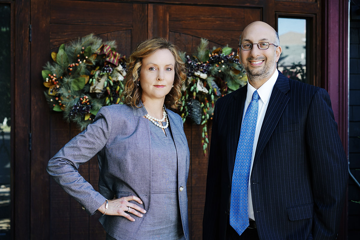Erica Harper and Rob Danesh standing outside of their office looking at camera.