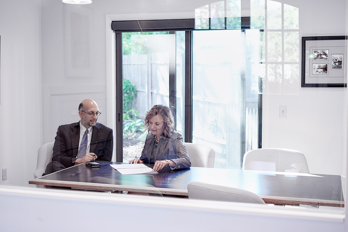 Rob Danesh and Erica Harper in a conference room discussing a report.