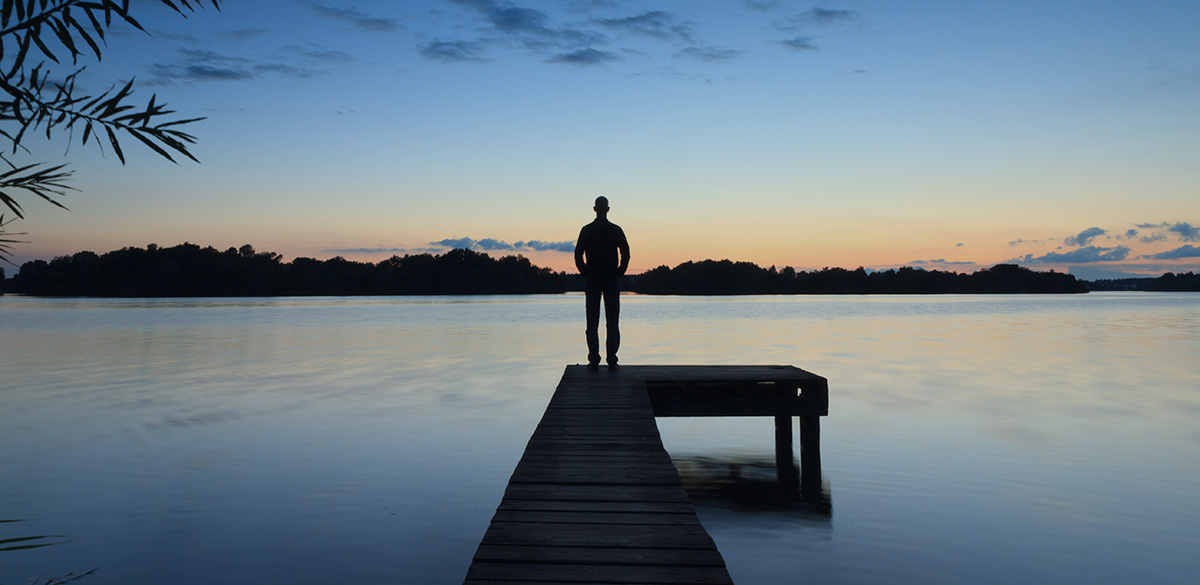 A silhouette of a person standing on a dock on the water after sunset.