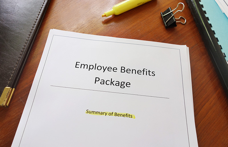 Employee Benefit Package on desk with document clips and highlighter.