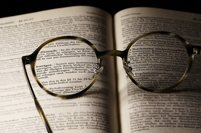 A pair of glasses on top of an open book.